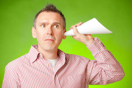 eavesdropper: Man listening with eartrumpet made of paper, could be a concept for eavesdropping, secrecy or curiosity Stock Photo
