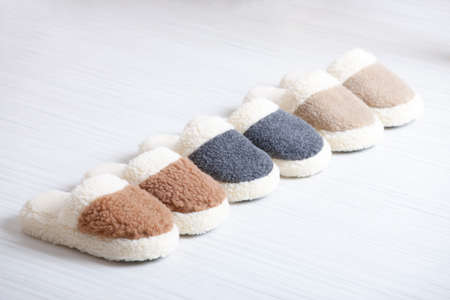 Three pair of natural woollen slippers on wooden floor Stock Photo - 20894681