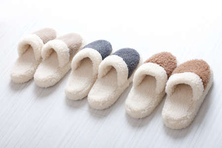 Three pair of natural woollen slippers on wooden floor Stock Photo - 20894682