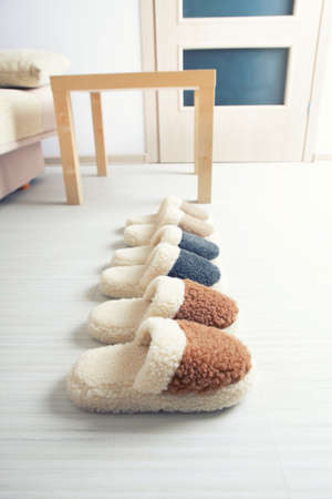 Three pair of natural woollen slippers on wooden floor in room Stock Photo - 20894684