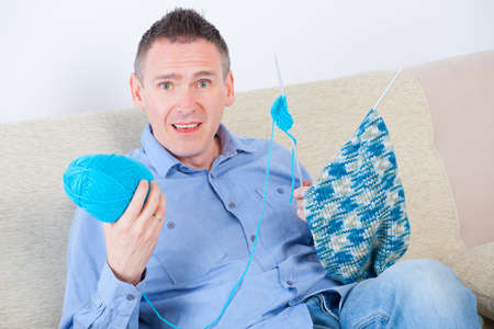 woll: Confused man sitting with knitting woll and needles Stock Photo