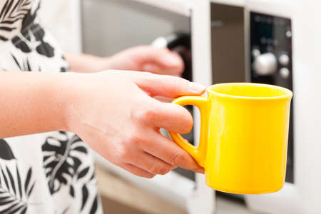 microwave oven: Opening the microwave oven with mug in the other hand Stock Photo