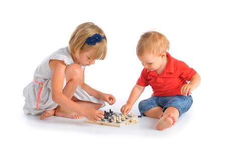 Girl and little boy playing chess isolated over white background photo