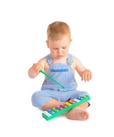 Cheerful baby boy playing on xylophone isolated over white background photo