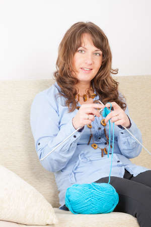 woll: Beautiful woman sitting with knitting woll and needles