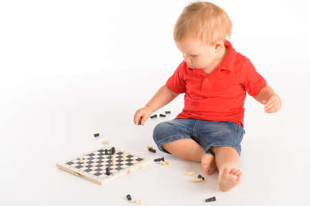 little boy playing chess isolated over white background photo