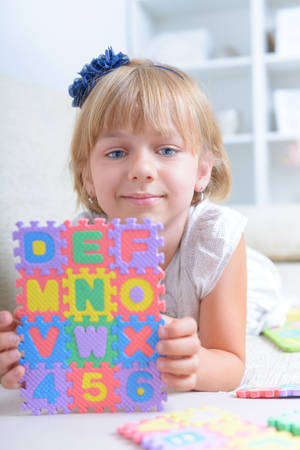 Beautiful blue eyed girl laying on the couch with alphabet letters puzzle photo