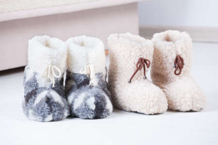 Two pair of natural woollen slippers on wooden floor Stock Photo - 23299387