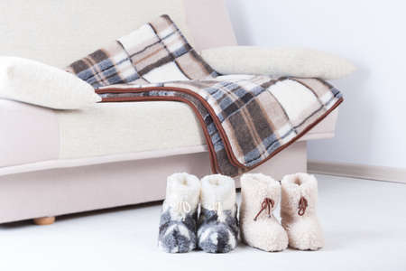 Two pair of natural woollen slippers on wooden floor and blanket on the couch Stock Photo - 23299388