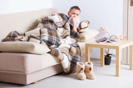 Man laying on sofa uder natural woolen blanket with tissue in his hand  photo