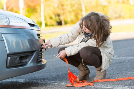 towing: Beautiful woman assembling towing hook to a broken car and holding tow rope in the other hand