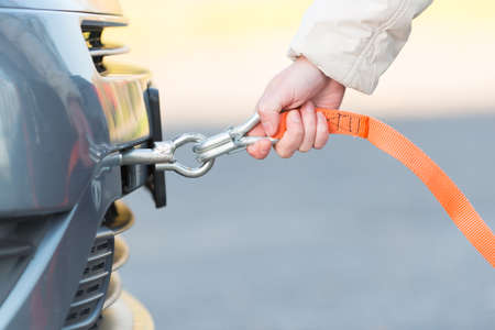towing: Hand holding tow rope near towing hook assembled to a broken car