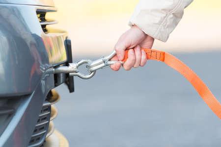 Hand hält Abschleppseil Nähe Anhängerkupplung montiert auf einem kaputten Auto