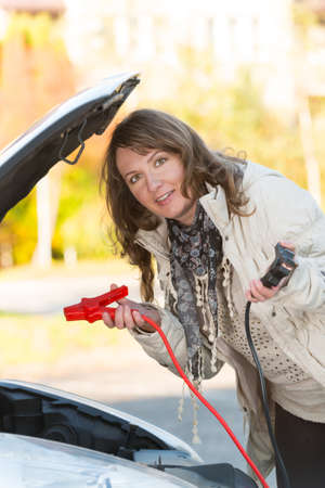 booster: Beautiful woman connecting booster cables to a car battery