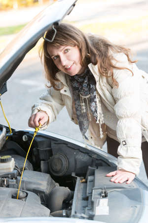 Beautiful woman checking engine oil level  photo