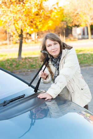 Beautiful woman picking up windscreen wiper and checking it photo