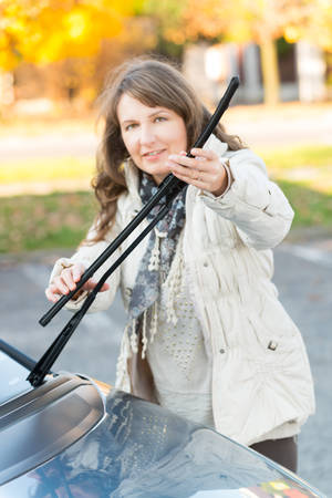 changing colors: Beautiful woman picking up windscreen wiper and checking it. Focus on hands. Stock Photo
