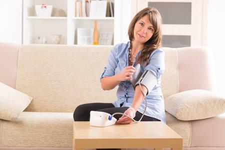 Schöne Frau die Kontrolle ihrer Blutdruck zu Hause Standard-Bild