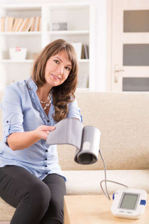young  cuffs: Beautiful woman checking her blood pressure at home and presenting pressure monitor cuff
