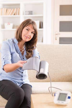 blood pressure cuff: Beautiful woman checking her blood pressure at home and presenting pressure monitor cuff