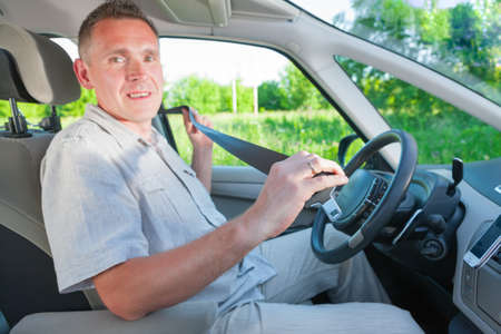 drive safely: Man driver with seatbelt in hand  Focus intentionaly left on hand
