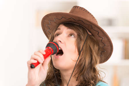 Beautiful woman wearing hat and singing with a red microphone photo