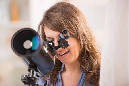 fernrohr: Schöne Frau, die durch astronomische Fernrohr gen Himmel stand in der Nähe eines Fensters