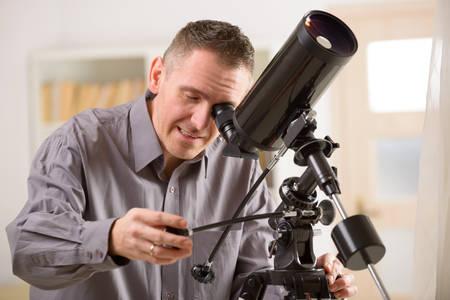Man looking skyward through astronomical telescope standing near a window photo