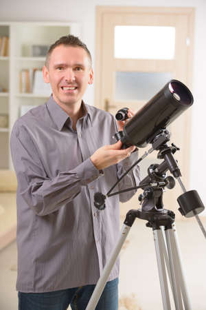 eyepiece: Man with astronomical telescope standing near a window with eyepiece in hand