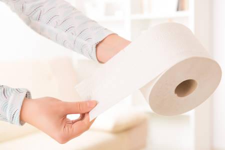 papel higienico: Mano que sostiene el papel higiénico en el hogar Foto de archivo