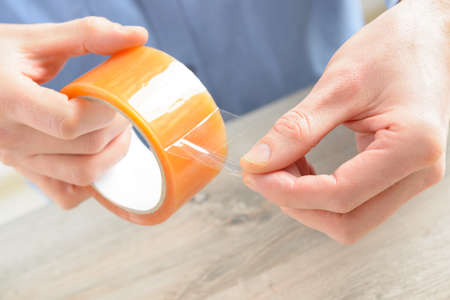 duct tape: Hands with roll of transparent packaging, adhesive tape  Stock Photo