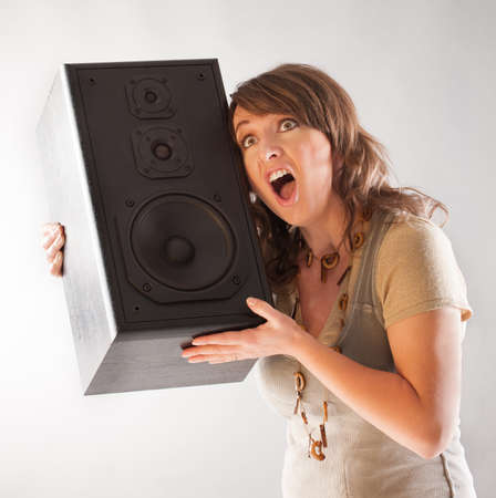 preamp: Young beautiful woman holding big wooden speaker and listening music