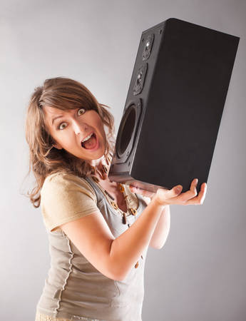 radio active: Young beautiful woman holding big wooden speaker and listening music