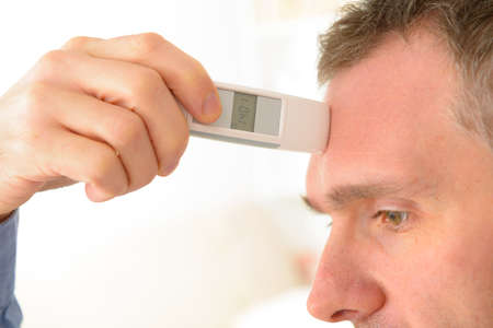 attempting: Man attempting to measure body temperature with thermometer on forehead Stock Photo