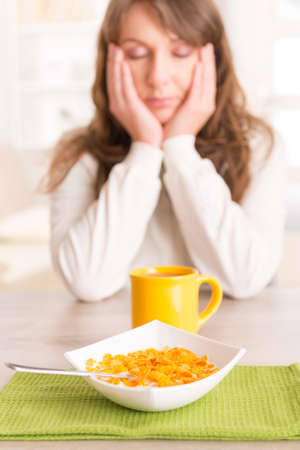 somnolent: Sleepy young woman trying to eat cornflakes and drink morning coffee