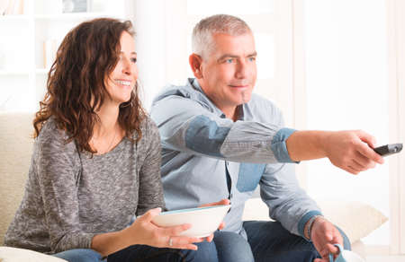 Cheerful mature couple sitting together and watching TV  photo