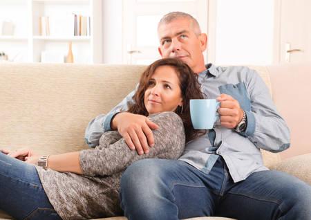 Glückliche erwachsene Paar sitzt auf Sofa im Haus lächelnd