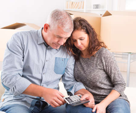 home expenses: Mature couple at new home sitting and using calculator to sum their expenses and loans