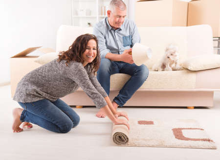 Happy mature couple unpacking in their new home, woman rolling carpet out and man fixing lamp photo