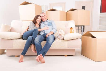 gente celebrando: Pareja madura feliz que celebra su nueva casa sentados juntos en el sofá con su pequeño perro sólo después de mudarse