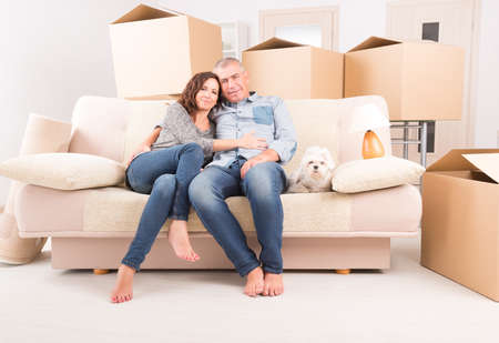 home buying: Happy mature couple celebrating their new home sitting together on the sofa with their little dog  just after moving in
