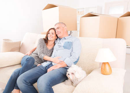 Happy mature couple celebrating their new home sitting together on the sofa with their little dog  just after moving in photo