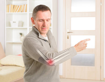 Man looking on his painful elbow, skeleton visible with marked pain area Stock Photo