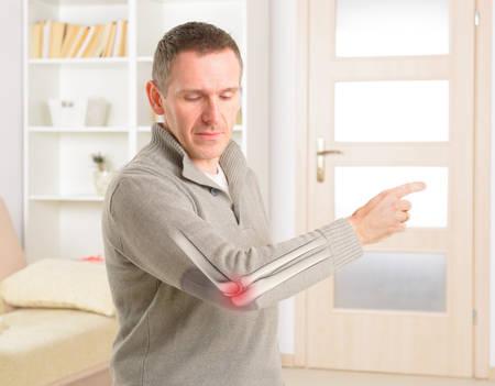 Mann sucht auf seinem schmerzhaften Ellenbogen, Skelett sichtbar mit deutlichen Schmerzbereich