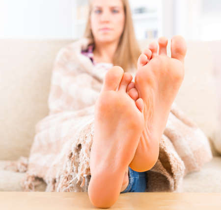 Young woman covered with blanket sitting on the sofa at home  Focus on feet