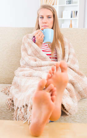 feet on desk: Bored young woman covered with blanket sitting on the sofa at home with feets on the table Stock Photo