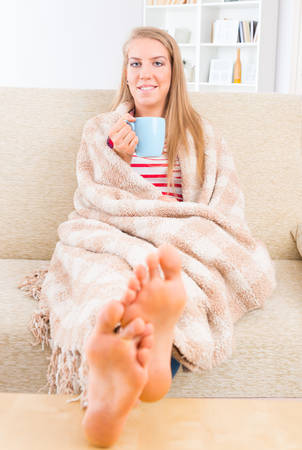 feet on desk: Smiling young woman covered with blanket sitting on the sofa at home with feets on the table