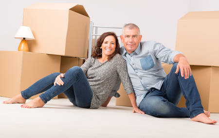 moving out: Happy mature couple unpacking boxes in their new home Stock Photo