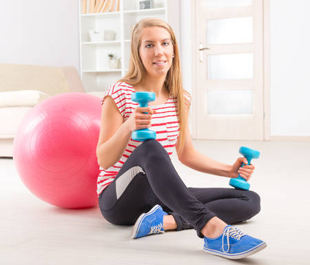 dumb bells: Beautiful young woman with gym ball and dumb bells exercising  Stock Photo