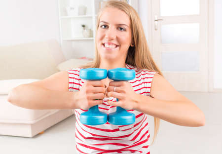 strengthen: Young woman doing exercise with dumb bell, strengthen her arms and shoulders at home